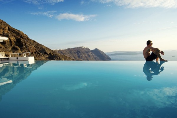 Man Sits On Edge of Infinity Pool Santorini Greece