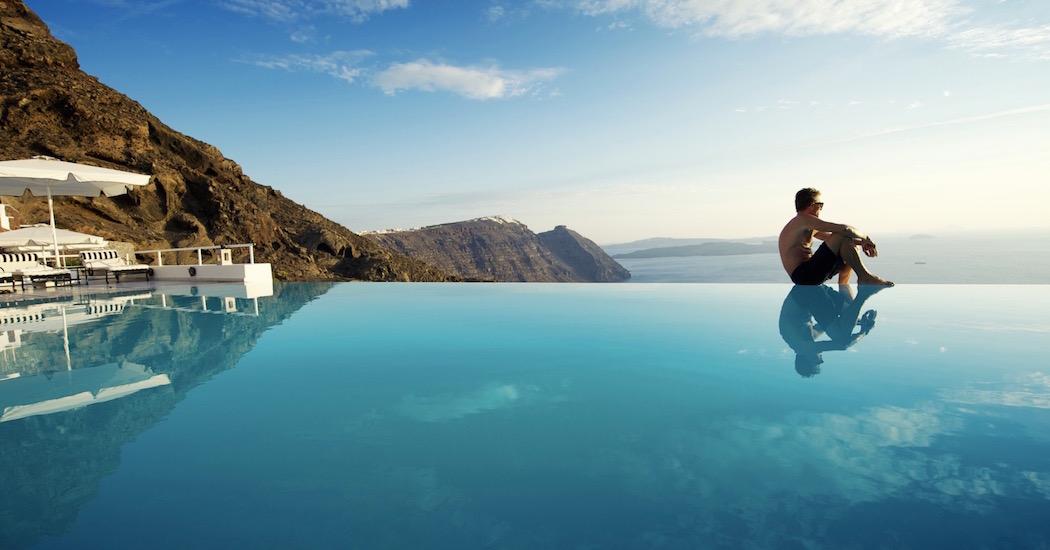 Man Sits On Edge of Infinity Pool Santorini Greece